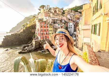 Young female traveler making selfie photo on the old coastal town in Riomaggiore in Italy. Happy vacations in Italy