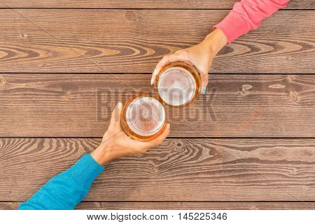 Cheers with beer over wooden table. Close up