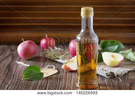 Apple Cider Vinegar In A Glass Bottle With Fresh Apples On A Table In A Rustic Style.