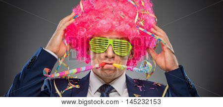 Funny businessman in pink wig and green glasses