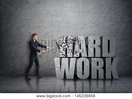 Side view of young businessman crashing 3D concrete 'hard work' words with a hammer. Efficiency at work. Succesful management. Business staff.