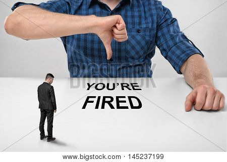 Small businessman with bowed head standing in front of cropped portrait of big boss showing thumb down with words 'you're fired' under his finger. Discharging and dismissing.