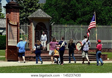 New Bern North Carolina - April 24 2016: Sunday afternoon Fife and Drum corps with flag bearer march out of the entry gate at 1770 Tryon Palace