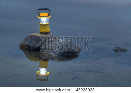 Night view of luminous hand lantern standing on the rock in the lake