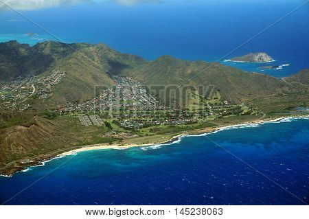 Aerial view of Sandy Beach and Koolua mountains on the south east corner of Oahu with clouds in the sky and off shore islands visible.