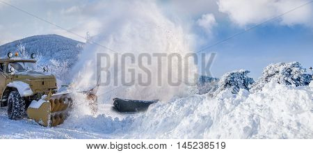 Snow plow machine blowing heavy snow while cleaning the road