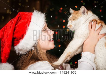 Happy little girl with a favorite cat in Christmas