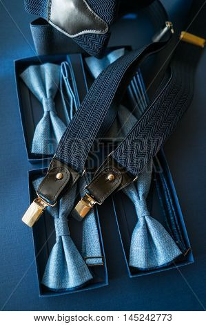 Men's costume accessories bow tie and suspenders on a blue background.