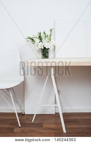 White scandinavian interior decor closeup: empty walls, designer chair, table and natural flowers.