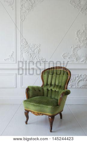 elegant green armchair in luxury clean bright white interior.