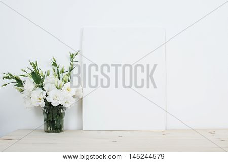 White interior decor, fresh natural flowers in vase and empty canvas on table