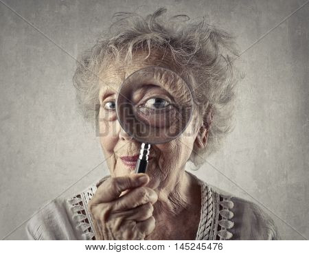Elderly woman looking through a magnifying glass
