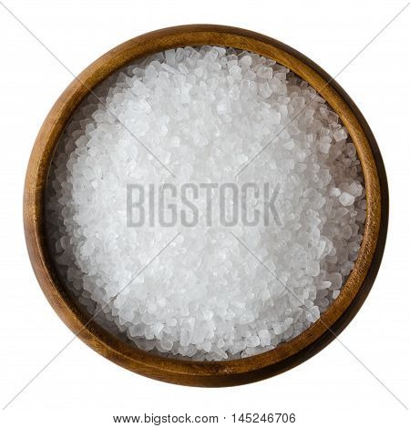 Sea salt in a wooden bowl on white background. Also called bay salt or solar salt, is used in cooking and cosmetics. Rough grained crystals of the mineral. Seasoning. Isolated macro photo close up.