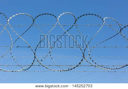 Barbed and razor wire security fence with blue sky