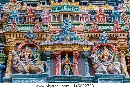 Madurai India - October 19 2013: Closeup of three times Meenakshi on North Gopuram. Twice she sits on a bull. Once she sits with Lord Shiva. In the central niche she stands alone. Pastel colors galore.