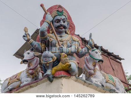 Madurai India - October 19 2013: Closeup of male Gana keeping guard on the corner of the Meenakshi Temple wall. Two bulls keep him company.