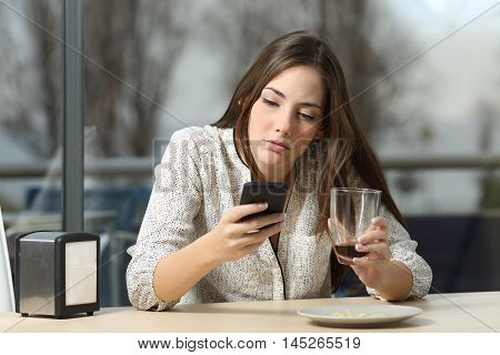 Angry woman in a coffee shop using a smart phone