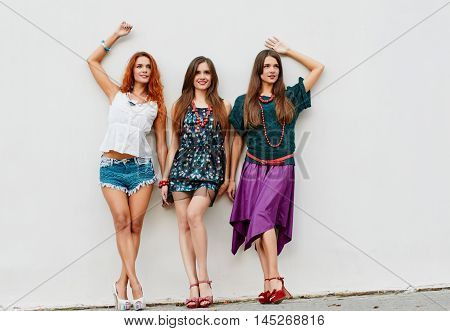 Girlfriends, sisters triplets Happiness portrait about light wall. full length