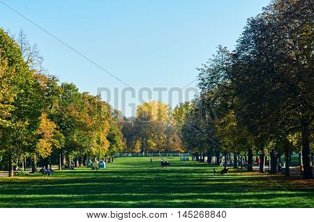Autumn Park at sunset. Autumn landscape. background with relaxing people on the grass. Bulgaria Sofia park Borisova Gradina