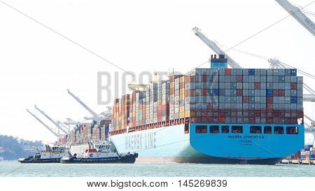Oakland CA - August 22 2016: Cargo Ships are unable to maneuver sideways. Tugboats ROBERT FRANCO and VETERAN pull cargo ship MAERSK EDMONTON from the dock to depart the Port of Oakland.