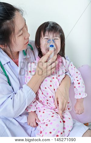 Closeup asian child having respiratory illness helped by doctor with inhaler. Pediatrician take care girl with asthma problems making inhalation with mask at hospital. child was bronchitis and crying.