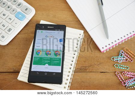 PHUKET, THAILAND AUG 18 2016 : Mobile phone with Google app on the splite screen and old wood desk with notepad and calculator Most of its profits are derived from AdWords