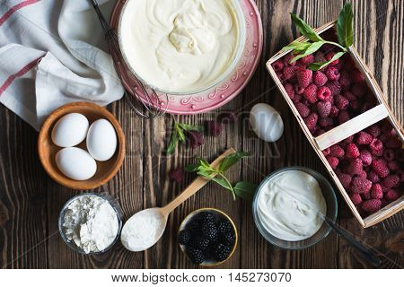 Making dough for berry pie. Ingredients for berry pie on a wooden background