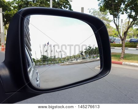 Rear car mirror and rear view of truck