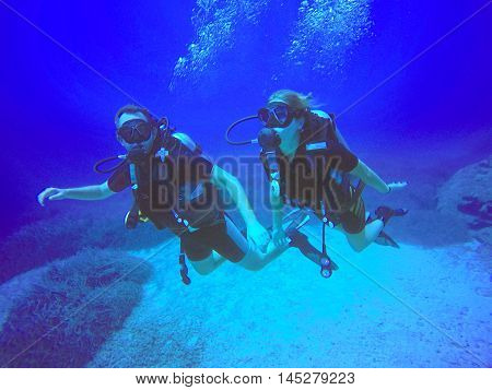 A scuba diver couple applying the buddy system. View of the scuba diver gear fins and bubbles underwater in the deep blue sea of Protaras Cyprus swimming.