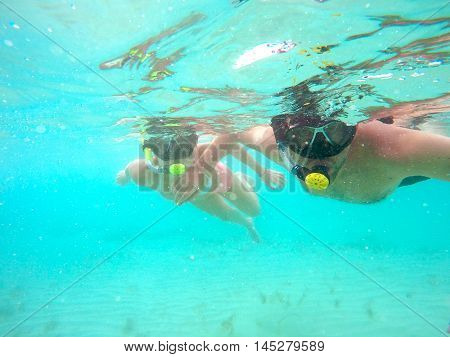 Portrait of a yound couple swimming underwater in the clean blue sea of Protaras Cyprus. View of snorkeling tube mask bikini of free divers near the surface of the water.
