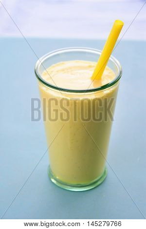 Mango lassi in glass with straw. Mango smoothie made with mango and yogurt yoghurt. Selective focus. Angle view.