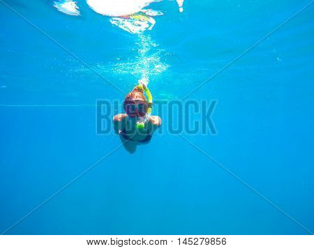 Portrait of a young woman swimming underwater in the clean blue sea of Limassol Cyprus. View of snorkeling tube mask bikini of free diver near the surface of the water.