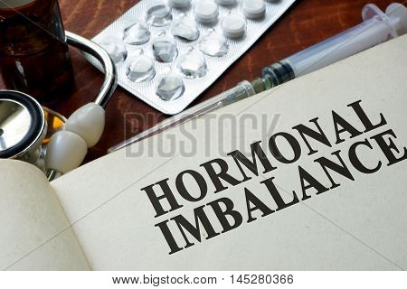 Book with words hormonal imbalance on a table.
