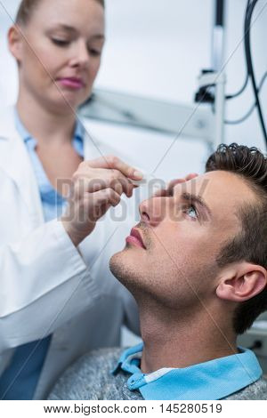 Female optometrist putting eye drop in patient eyes in ophthalmology clinic