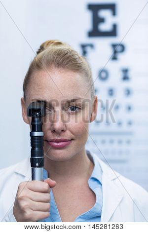 Close-up of female optometrist looking through ophthalmoscope in ophthalmology clinic