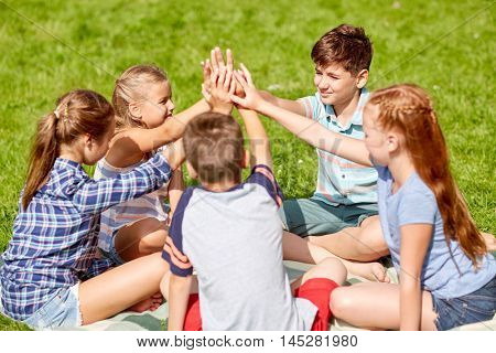 summer holidays, friendship, childhood, leisure and people concept - group of happy pre-teen kids making high five gesture in park