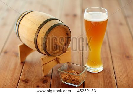 brewery, drinks and alcohol concept - close up of draft lager beer in glass, peanuts and wooden barrel on table