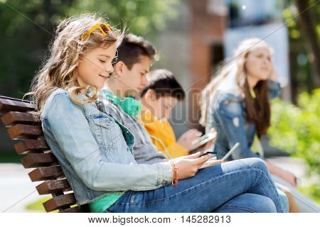technology, internet and people concept - happy girl with tablet pc computer and group of teenage friends or students outdoors