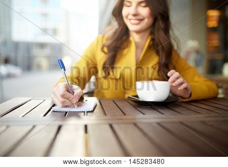 leisure and people concept - happy young woman or teenage girl with cup drinking cappucino and writing to notebook at city street cafe terrace