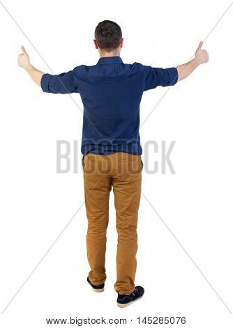 Back view of business man shows thumbs up. man in a blue shirt with the sleeves rolled up showing happy thumbs up.