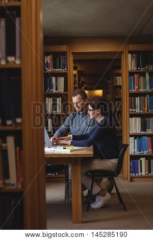 Mature students working together with laptop in college library