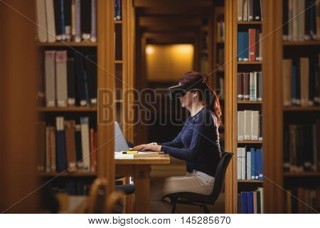 Mature student in virtual reality headset using laptop to help with studying at college library