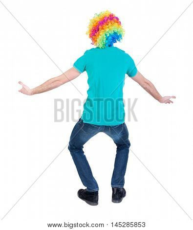 back view of dancing young beautiful man in clown wig. Curly man in a turquoise sweater and clown wig squats.