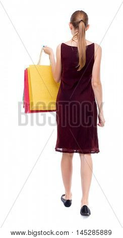 back view of going woman with shopping bags . Isolated over white background. The girl in the maroon sleeveless dress goes shopping.
