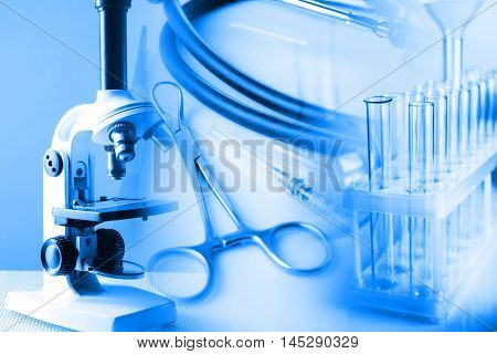 Microscope with surgery instruments and test tubes in laboratory on light blue background