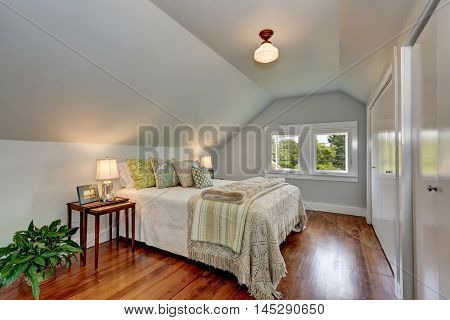 Attic Bedroom Interior With Vaulted Ceiling And Hardwood Floor.