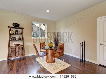 Dining Room With Round Glass Table And Wooden Chairs