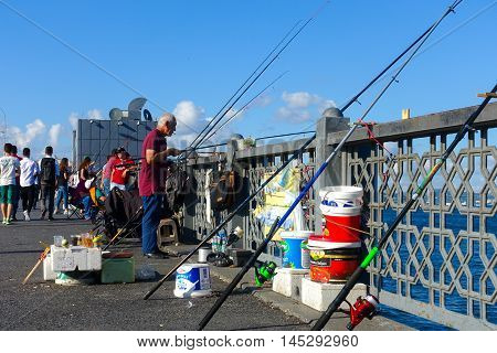 Istanbul Turkey - July 5 2016: Fishermen surrounded by their fishing equipment and cold drinks are fishing on the Galata Bridge at 17.30 in the evening. Fishing from the Galata Bridge is an everyday activity.