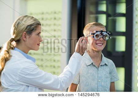 Female optometrist examining young patient with phoropter in ophthalmology clinic