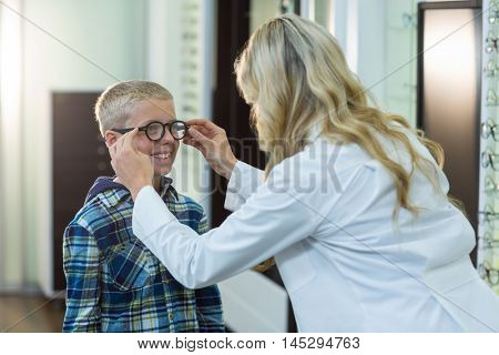 Female optometrist prescribing spectacles to young patient in ophthalmology clinic